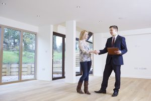 Woman Shaking Hands With Estate Agent In New Home